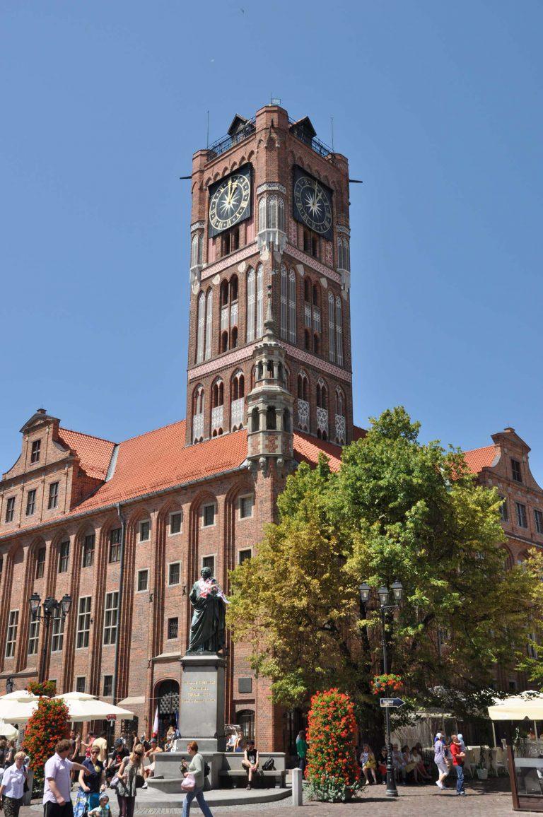 Pomnik Mikołaja Kopernika, w tle ratusz z wieżą zegarową, Toruń, Polska
